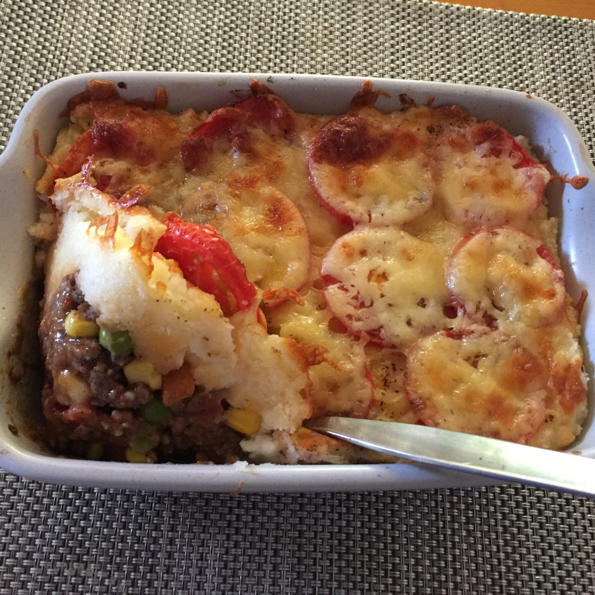 Beef shepherd's pie, savoury beef and vegetables topped with mashed potato - sliced tomatoes and melted cheese