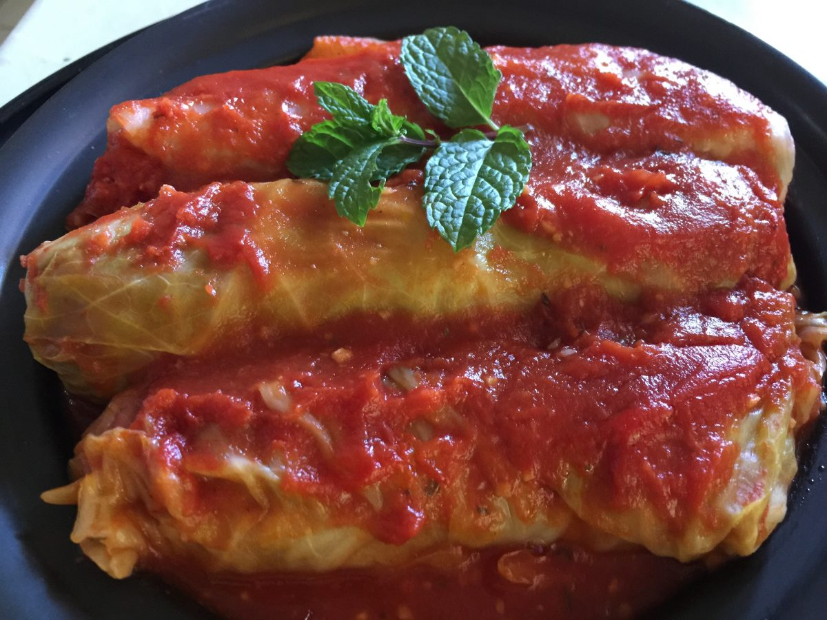 stuffed cabbage rolls filled with mince an rice covered in tomato puree, garlic and dried mint served on black plate