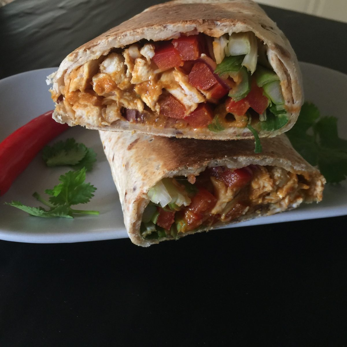 Satay Chicken Toasted wrap by cookingmealsforone.com is made by combining a good quality satay sauce with cooked chicken and placing in a wrap with slices of red capsicum-green onion wrapped tight and toasted in a sandwich press