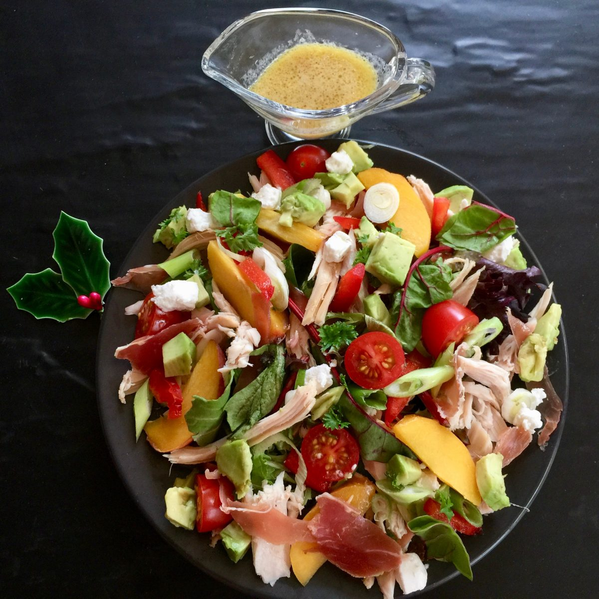 a vibrant salad filled with avocado, lettuce, cooked chicken, wedges of fresh peaches, halved cherry tomatoes, red chilli, mixed lettuce, baby spinach, rocket, avocado, prosciutto, goats cheese, green shallots, served with a dijon mustard vinegarette
