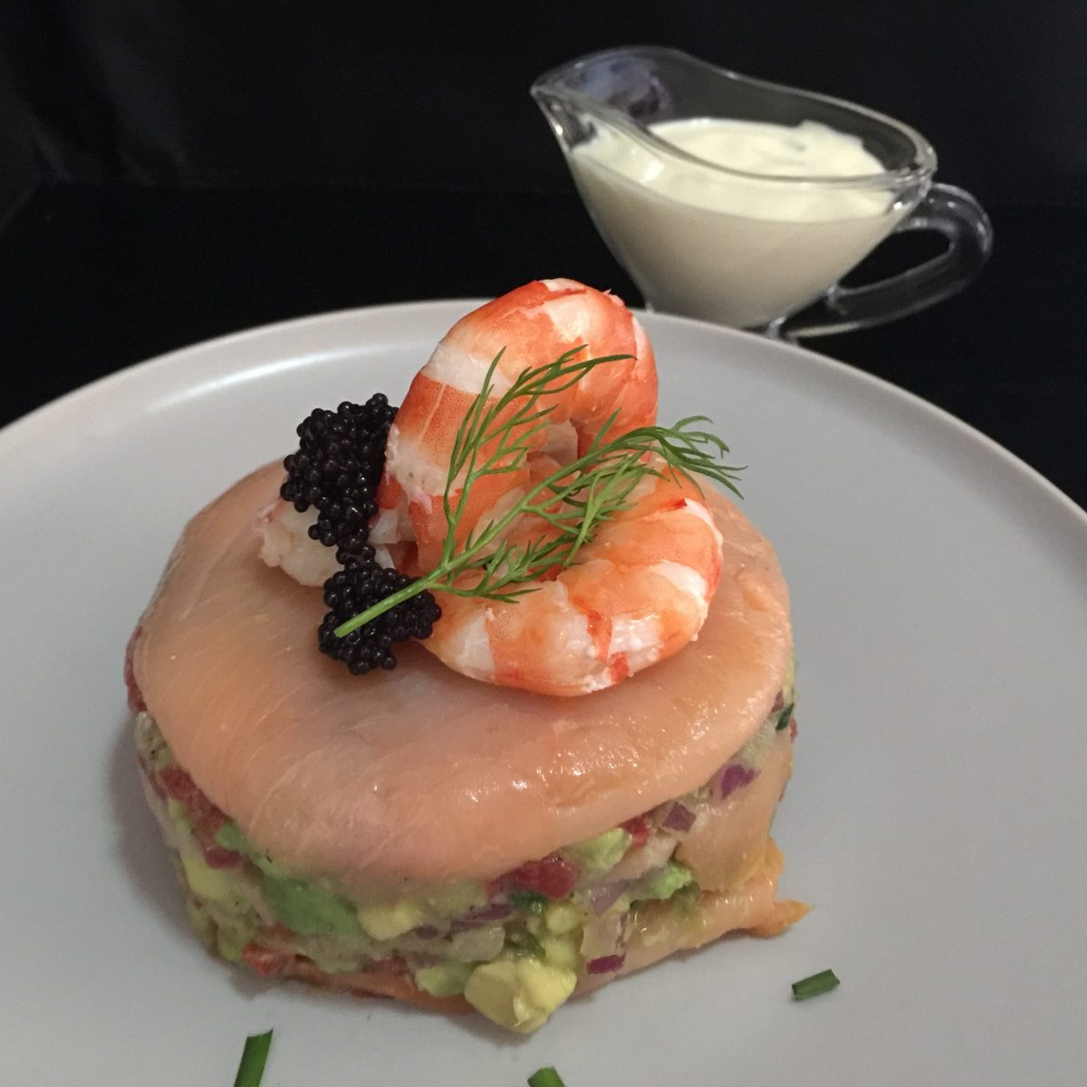 layers of smoked salmon lemony avocado salsa topped with 3 fresh ly peeled prawns and a little black caviar with a sprig of dill and lemony mayonnaise dressing with chopped dill or chives on the side by cooking meals for one