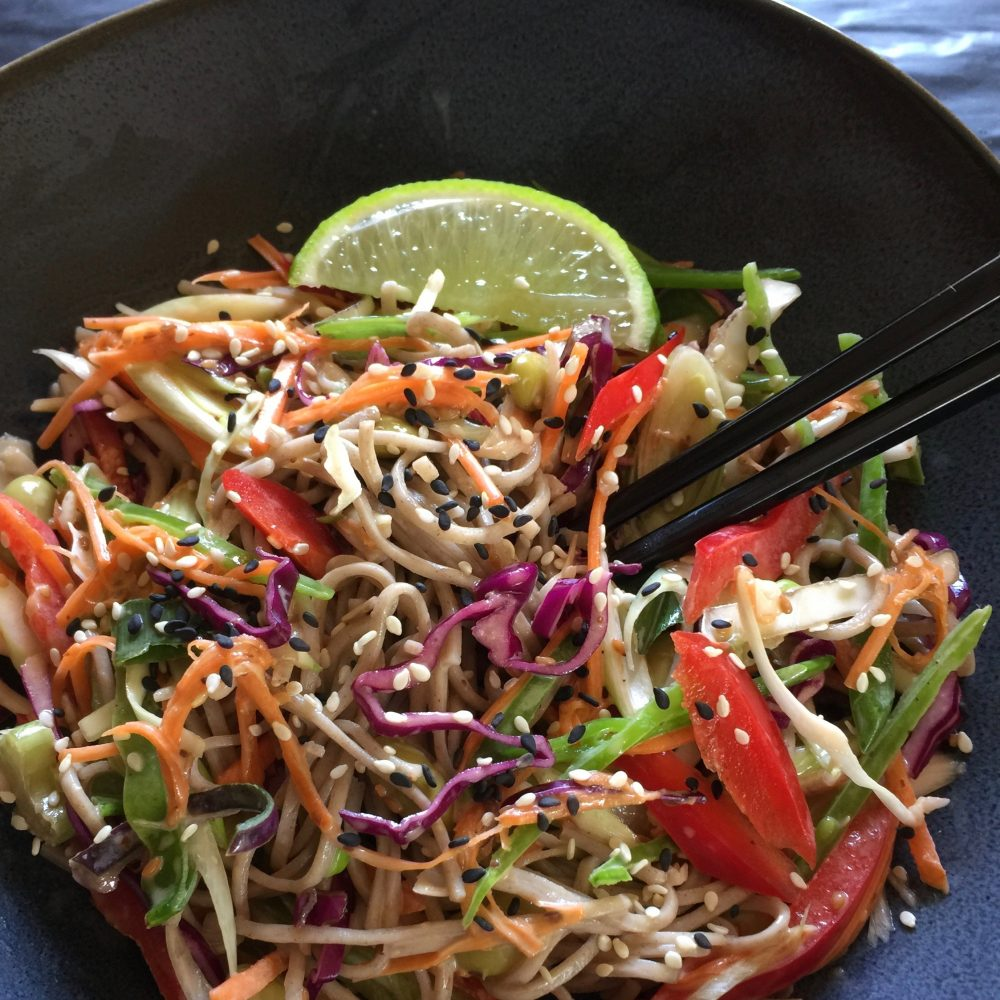 This delicious salad is healthy vibrant and colouful, full of crunchy red and green cabbage, carrots, capsicum, and soba noodles dressed in a delicious Japanese Roasted sesame, lime and soy dressing. Served in a salad bowl with chopped sticks on the side