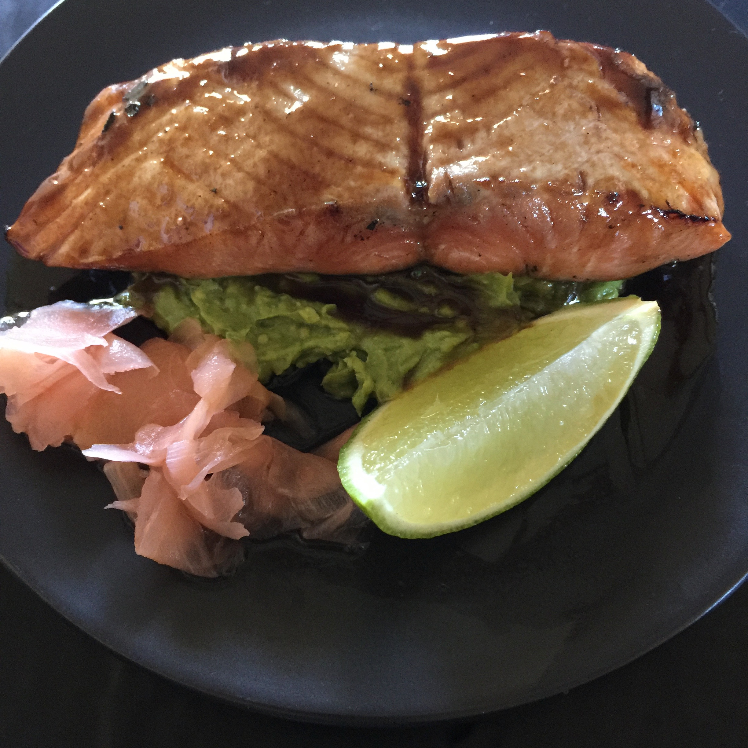 A fillet of smoked salmon dressed in a delicious teriyaki sauce served with smashed wasabi avocado, pickled ginger with a wedge of lime on a black plate by cooking meals for one