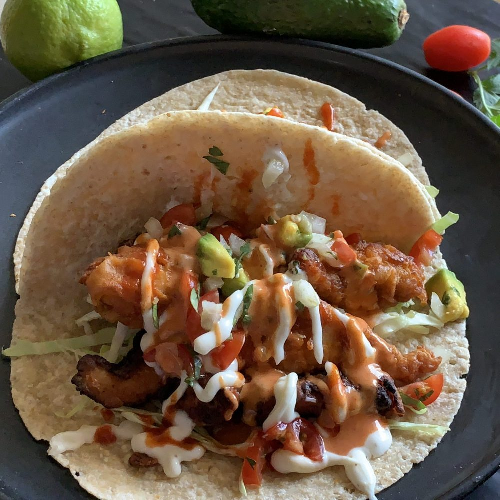 A delicious combination of crispy shredded green cabbage, then a avocado, tomato and onion salsa topped with Korean flavoured pan friend chicken pieces placed in the middle of a soft taco wrap . Drizzled with a Sriracha and Mayo sauce and Aioli . Served on a black plate. Enjoy!