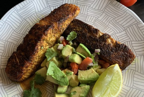 2 juicy salmon fillets coated in Moroccan Spices and pan seared in melted butter until blackened and just cooked. Served with an Avocado Salsa of avocado chunks chopped red onion cherry tomatoes coriander and dressed in lime juice Served on a patterned white plate with a wedge of lime