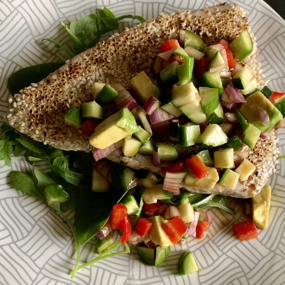 A tuna steak seared and crusted with sesame seeds served with avocado salad and a wasabi, mirin, soy sauce, olive oil and lime juice dressing. Yum