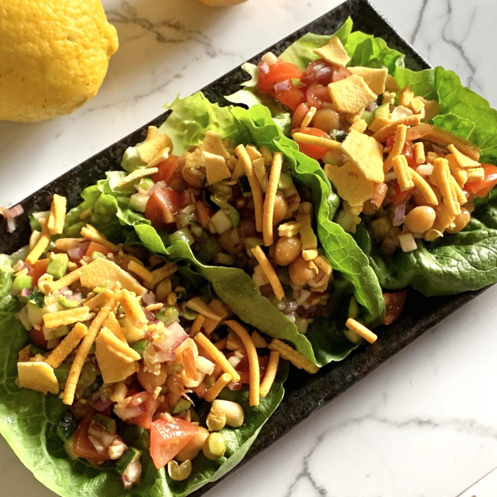 A combination of tomatoes, cucumber, red onion, coriander, cumin, chopped peanuts and Bombay mix, cooked chic peas tossed in taramind paste, sweet chilli oil, and lemon juice. Served on 3 freshly washed cos lettuce leaves served on a black plate by cookingmealsforone.com