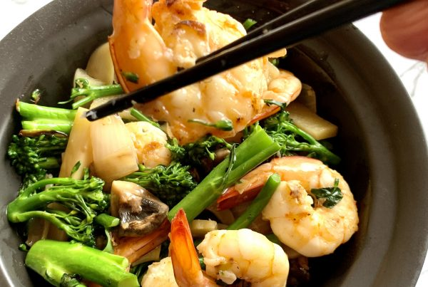Braised Prawns with Broccolini served with a Chinese style gravy in a black bowl