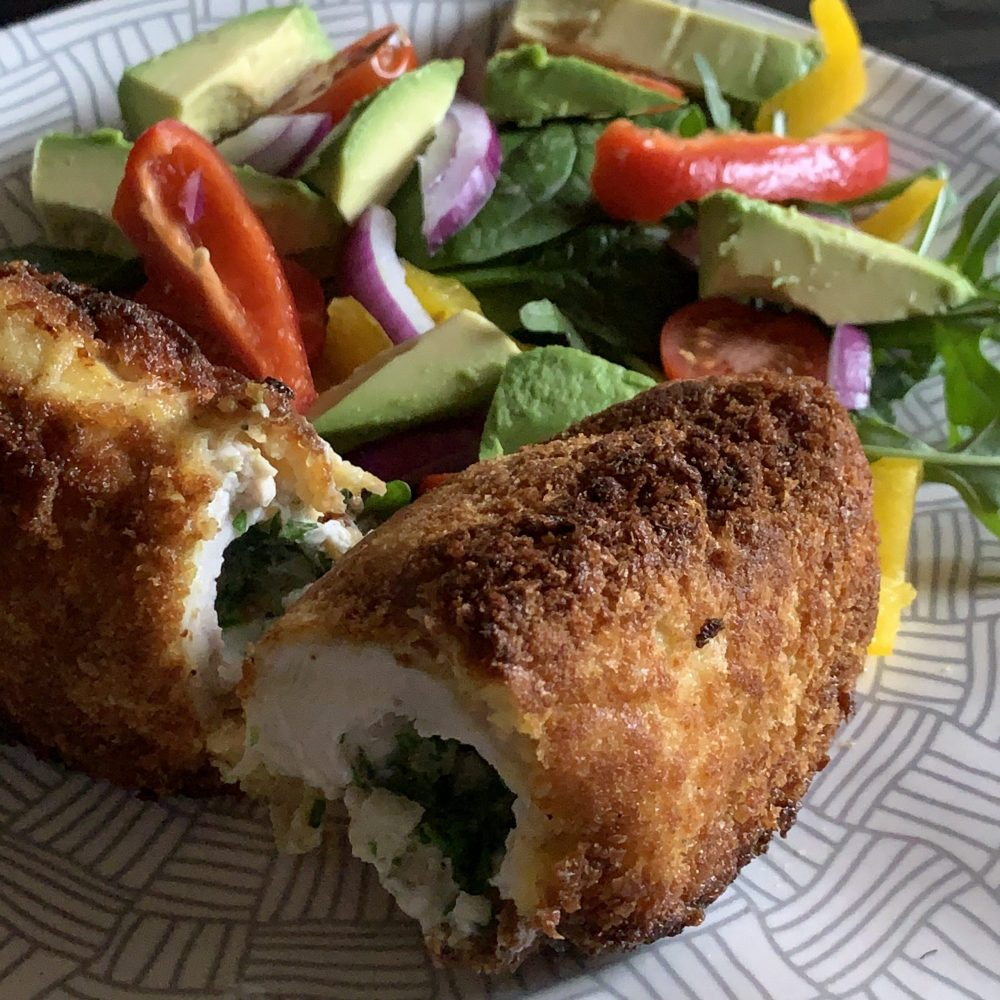 Crunchy-Crispy Chicken breast stuffed with a tangy-garlic-butter rolled and coated in panko breadcrumbs.Then Then pan fried to a golden crunch and cooked in the oven. served with a crisp salad